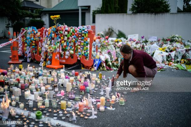 A student places a candle next to flower tributes for the victims after a vigil in Christchurch on March 18 three days after a shooting incident at...