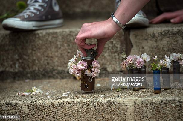 A student places on a step a grenade filled with flowers next to rubber bullets used during a mass protest of the Fees Must Fall movement at the...
