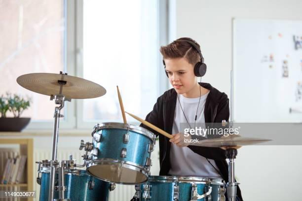 student beim trommeln spielen, während sie musik in der klasse hören - izusek stock-fotos und bilder