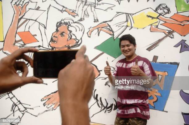 A student poses for a photo in front of a newly made Mural at a wall of the Central Shahid Minar as part of the observance of for International...