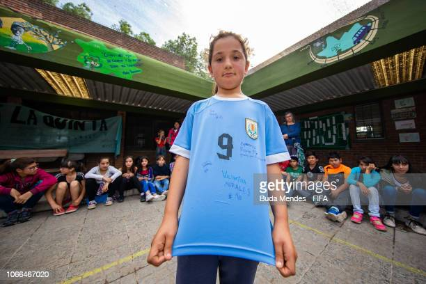 Student poses for a photo with her autographed jersey by the players of the Uruguay team during a meeting at Escola 355 during the FIFA U-17 Women's...
