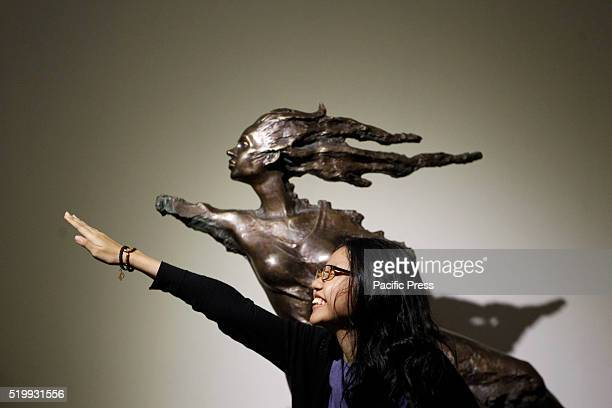 A student poses near a sculpture by Indonesian artist Purjito at National Gallery in Jakarta during Christmas holiday