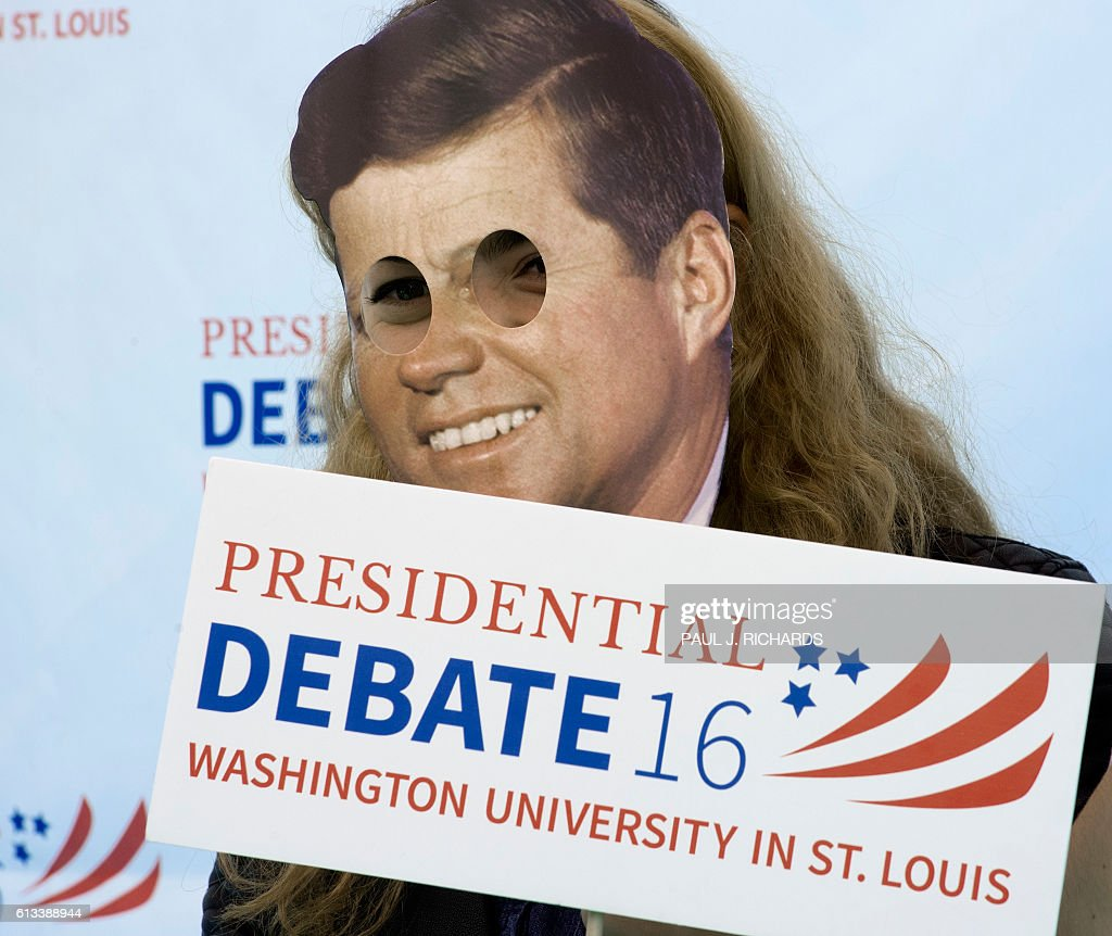 A student poses with an image of US President John F. Kennedy and debate signs outside the site of the second Presidential debate October 8, 2016, at Washington University in St. Louis, Missouri. US Presidential Republican nominees Donald Trump and Democrat nominee Hillary Clinton will debate for the second time in St. Louis on October 9. / AFP / PAUL
