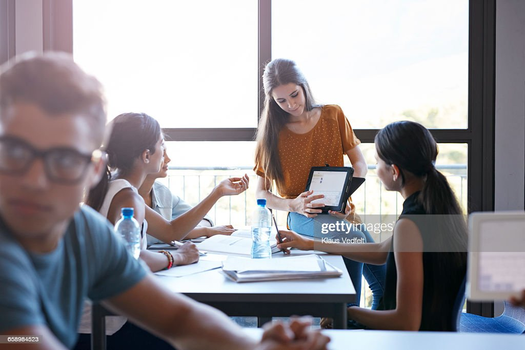 Student presenting project on tablet, to group : Stock Photo