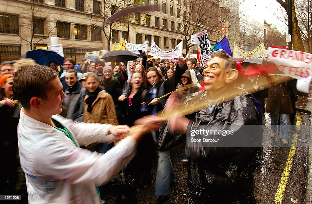 A student pretends to hit a fellow student wearing a mask of British Prime Minister Tony Blair (R) during a demonstration December 4, 2002 in London, England. Thousands of students marched through the streets of London to protest against student debt and any increase in fees.