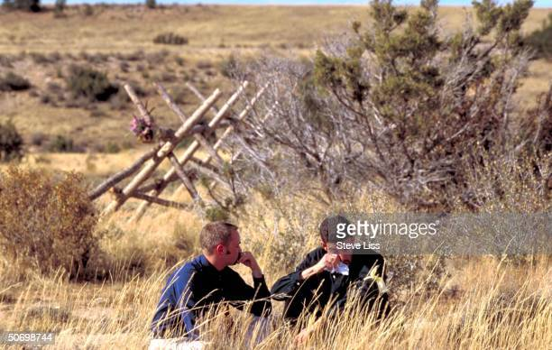 Student professor mourning death of their friend Matthew Shepard openly gay Univ of Wyoming student by fence where he was left tied near death from...