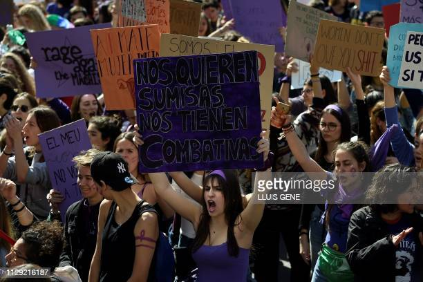 Student protesters hold signs including 'They want us submissive they have us combative' during a demonstration marking International Women's Day in...