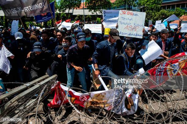 Student protesters step on barbed wire during a rally in Surabaya East java province on September 25 against the government's proposed change in its...
