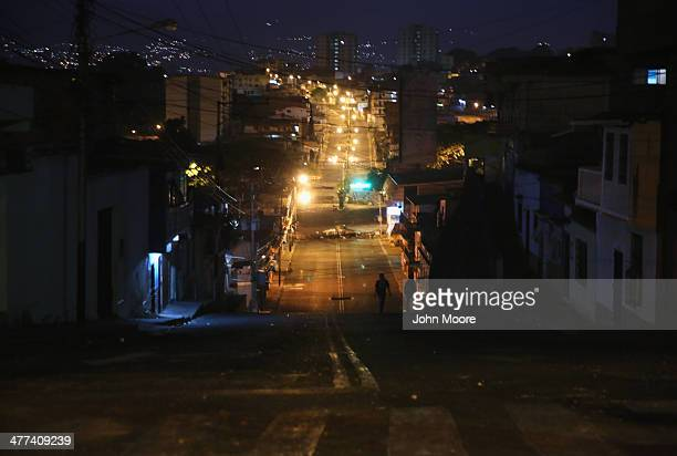 Student protesters walk between antigovernment barricades before dawn on March 9 2014 in San Cristobal the capital of Tachira state Venezuela Local...