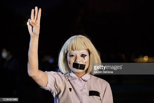 Student protestors hold up a three finger salute and tape their mouths shut during a demonstration at Mahidol University on August 18, 2020 in...