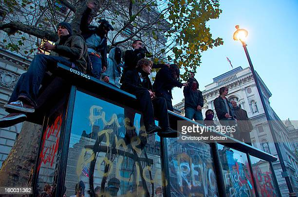 Student protestors on top a bus shelter in Whitehall London during the G20 Demonstrations November 2010