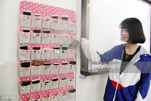A student puts a mobile phone into the bag storing students' mobile phones before class in a vocational and technical school at Tonglu County on...