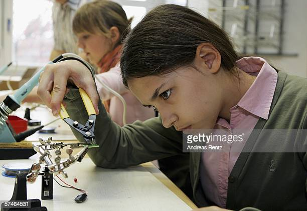 Student Rahel Marschall uses pliers on an electronic circuit at the electronics lab of the FritzHaber Institute on April 27 2006 in Berlin Germany...
