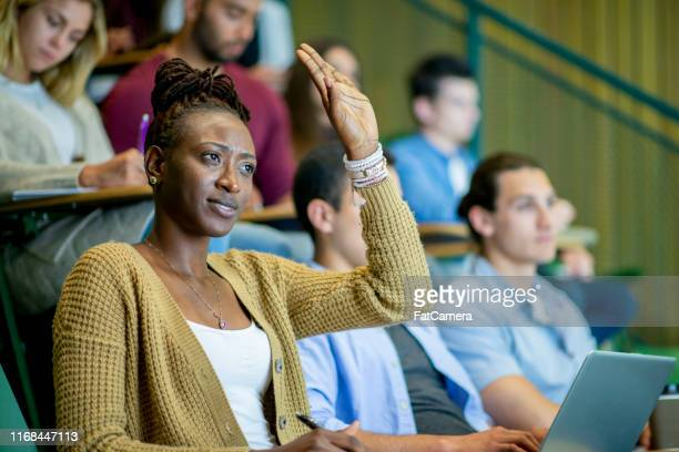 student raises her hand in a lecture hall - community college stock pictures, royalty-free photos & images