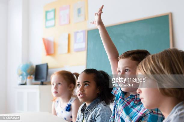 student raising hand in classroom - hand raised stock pictures, royalty-free photos & images