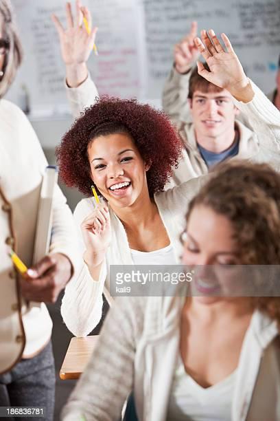 Student raising hands in class