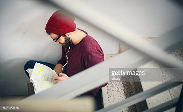 student reading a book in hallway. - music halls stock pictures, royalty-free photos & images