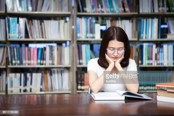 student reading a book in library. - literature stock pictures, royalty-free photos & images