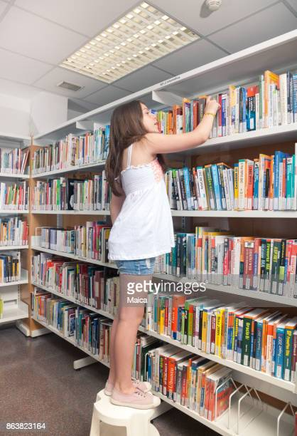 Student reading book between the shelves in the library