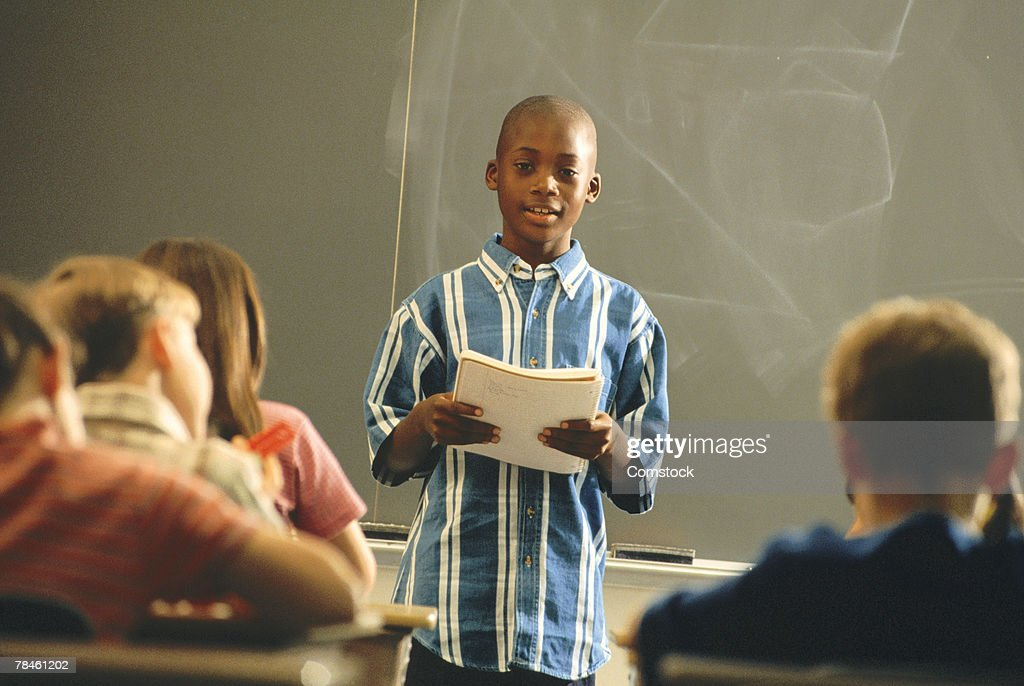 Student reading report in front of class : Stock Photo