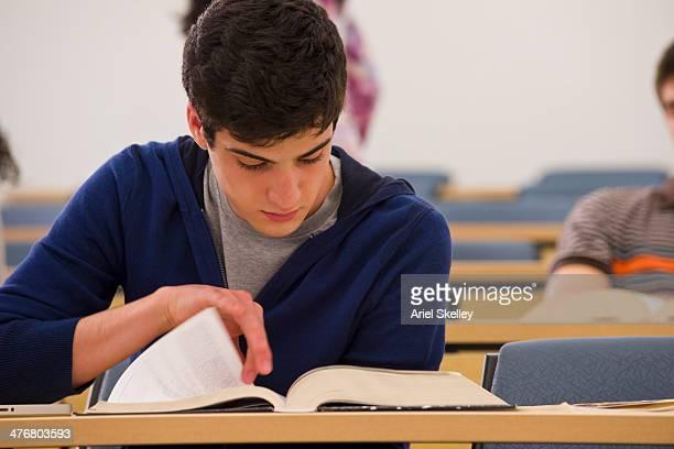 student reading textbook in classroom - ティーンエイジャーのみ ストックフォトと画像