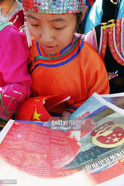 Student reads a special edition newspaper carrying a report on China's first manned spaceship on October 16, 2003 in Beijing, China. China launched...