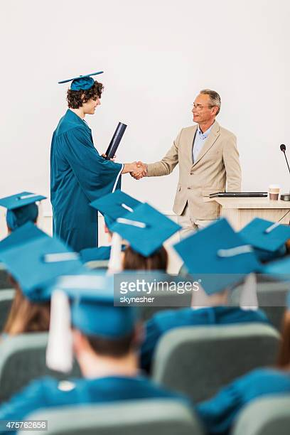 Student receiving diploma and shaking hands with professor.