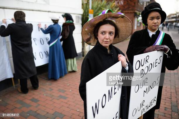 Student Rosa Higgs poses with a placard while a group recreate a suffragette protest march through the town centre at Royal Holloway University of...