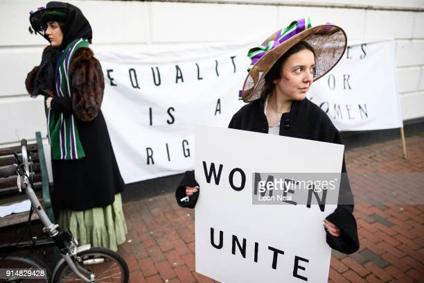 Student Rosa Higgs stands with a placard while a group recreate a suffragette protest march through the town centre at Royal Holloway University of...