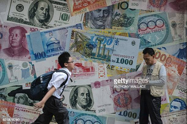 A student runs past a man checking his phone in front of a display showing bank notes of different currencies in Hong Kong on November 9 2016 Share...