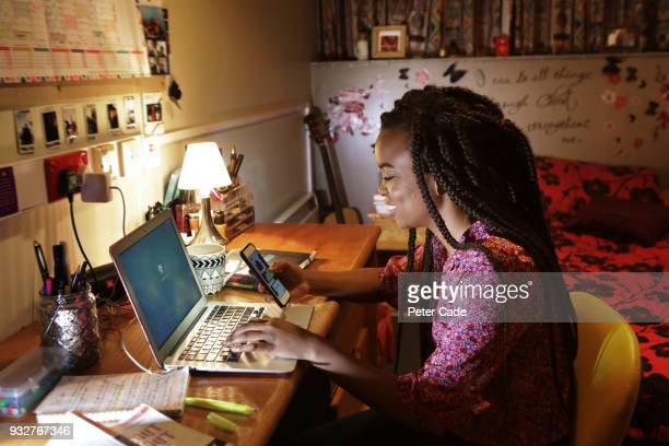 student sat at desk in bedroom looking at phone - home schooling stock pictures, royalty-free photos & images