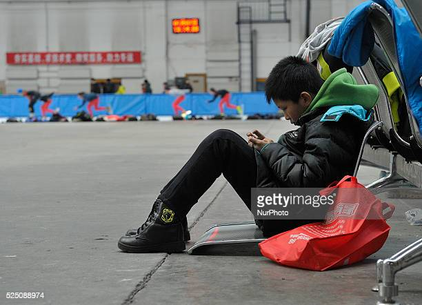A student see smartphone at gymnasium to relax Harbin ice and snow school in Harbin city of China on Jan 7 2016Harbin ice and snow sports school...