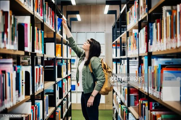 student selecting book from shelf in library - library stock pictures, royalty-free photos & images