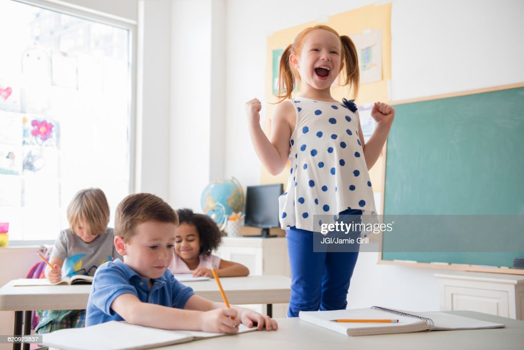 Student shouting at desk in classroom : Stock Photo