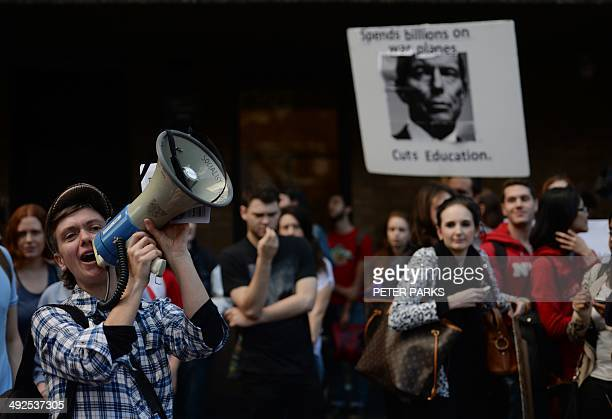 A student shouts through a megaphone next to a placard with Australian Prime Minister Tony Abbott on it at a protest by students at Sydney University...