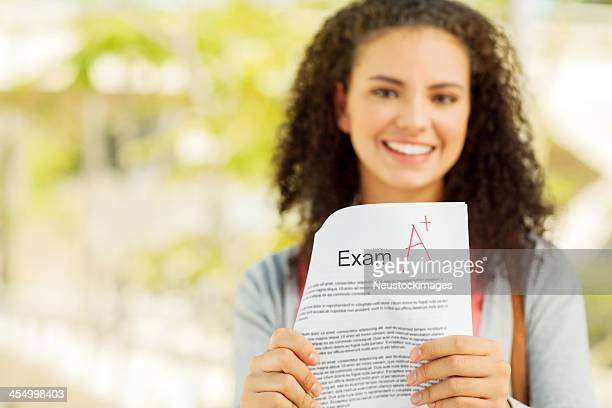 Student Showing Exam Result With A+ Grade On Campus