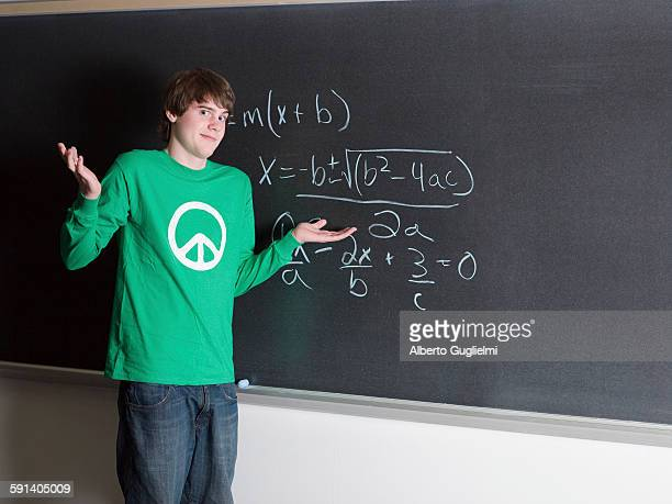 Student shrugging in confusion at chalkboard in classroom