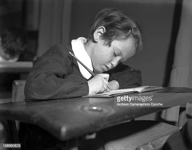 A student sits at his desk and writes with a cartridge pen in an unidentified boys' school Venice Italy 1949