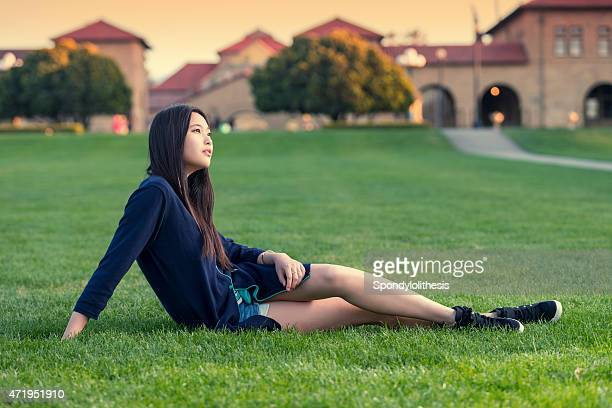 Student  sitting on the  campus green grass