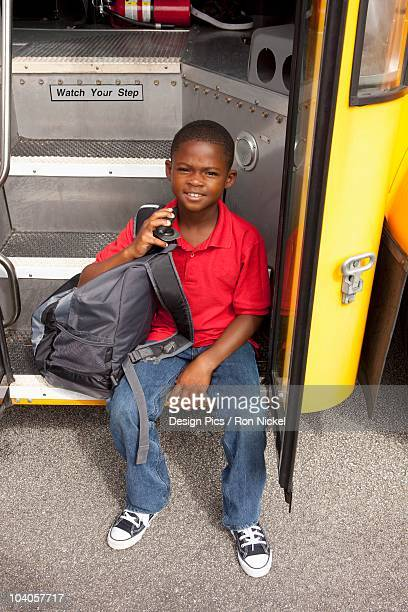 Student Sitting On The Step Of The School Bus