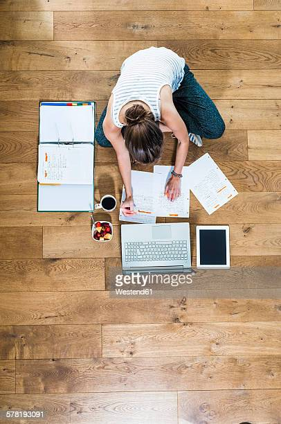 Student sitting on wooden floor surrounded by papers, laptop, digital tablet, file folder, coffee and fruit bowl