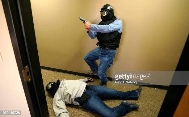 A student slowly moves by a mock shooting victim during a Tac*One Consulting 'Lone Wolf' civilian active shooter response course for concealed...