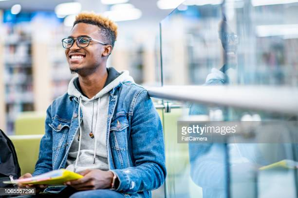 student smiles while studying in a library - bleached hair stock photos and pictures