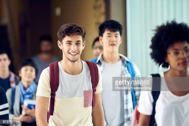 student smiling as he walks between classes - femme entre deux hommes photos et images de collection