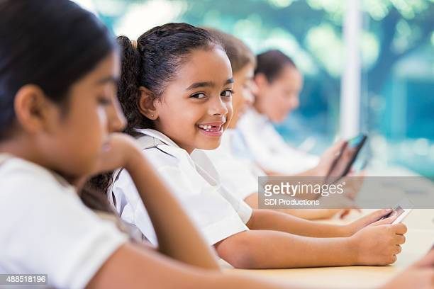Student smiling in private elementary school while using technology
