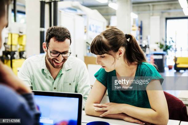 student smiling while doing work with a lab partner - wissenschaft und technik stock-fotos und bilder