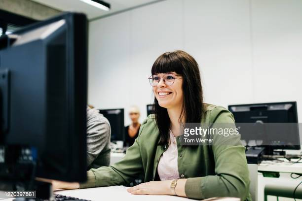 student smiling while working during seminar - wissenschaft und technik stock-fotos und bilder