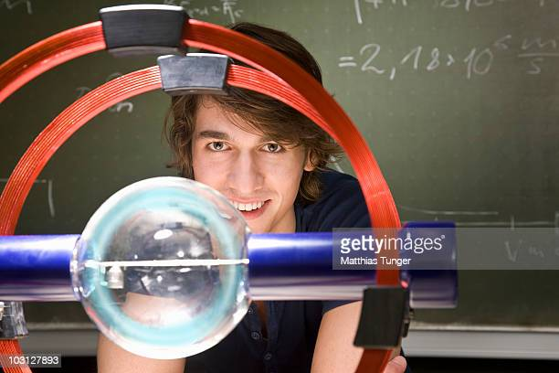 student smiling with experiment in foreground - physik stock-fotos und bilder