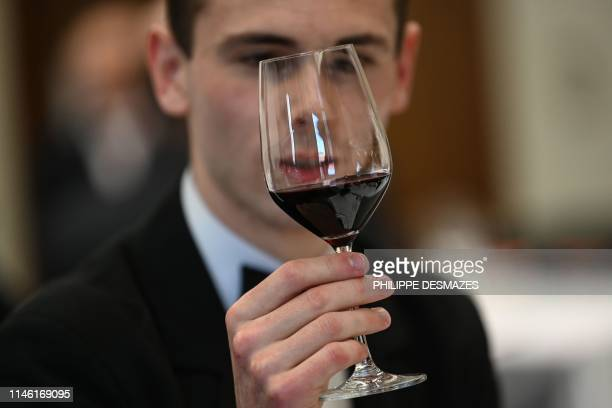 A student sommelier looks at a glass of red wine during the 27th contest for the best student sommelier on May 24 in Tain l'Hermitage southeastern...