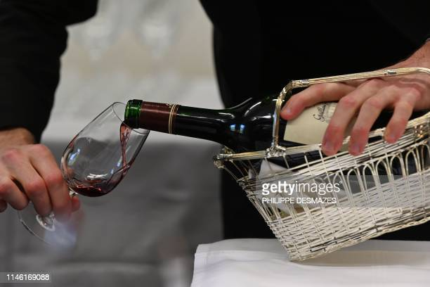 A student sommelier serves a glass of red wine during the 27th contest for the best student sommelier on May 24 in Tain l'Hermitage southeastern...